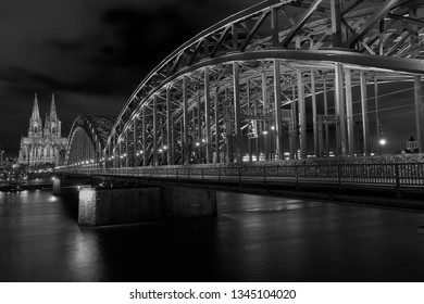 Cologne Cathedral, Hohenzollern Bridge Panorama with dark sky, view over the Rhine to the famous Cologne motif whose bridge leads to Cologne Central Station and the Old Town. Black and White.