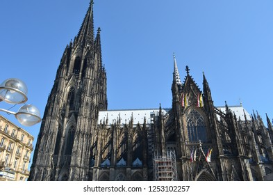 Cologne Cathedral is seen against a blue sky. Modern lights in the foreground make a contrast with the old building.