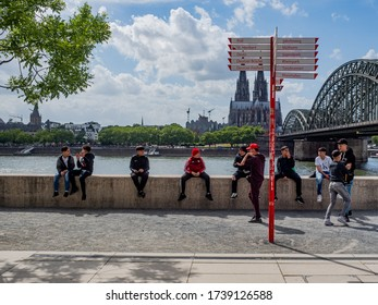 Cologne, Germany, 23 May 2020. Gang of kids sitting on a wall on the river Rhine on a sunnay day with Cologne Cathedral and Hohenzollern Bridge in the background.