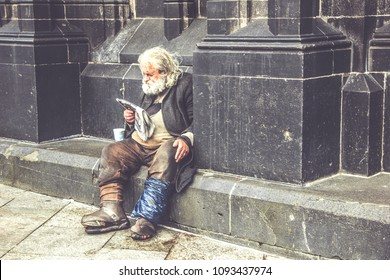 COLOGNE, GERMANY - April 16, 2018: A homeless tramp reads a newspaper sitting on the street near the cathedral