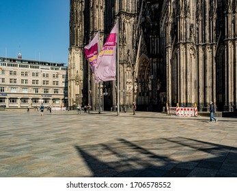 """Cologne, Germany, April 2020. Empty """"Domplatte"""" square in front of majestic Cologne cathedral in the afternoon sun during Corona lockdown."""