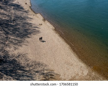 Cologne, Germany, April 2020. Two lonely people walking across a stone beach on the bank of the river Rhine at low water.