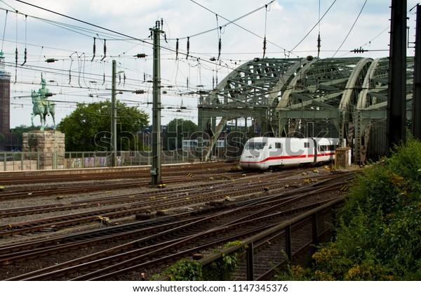 COLOGNE, GERMANY – AUGUST 07, 2014: Central Station´s rails with Hohenzollern bridge and a high speed train arriving