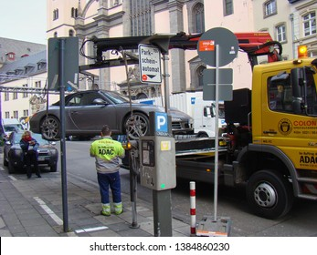 Cologne, Germany - August 2015: Expensive Porsche sports car gets lifted up onto tow truck by parking enforement patrol in downtown Cologne.