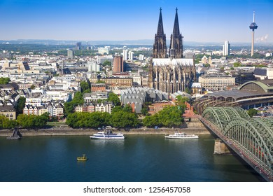 Cologne, Germany- August 22, 2015 - Roman Catholic Gothic Cathedral, Colonius TV Tower, main train station and  Hohenzollern Bridge, aerial view from the other side of Rhine river.