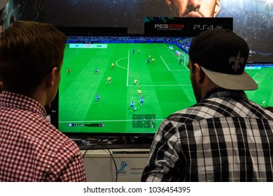 Cologne, Germany - August 24, 2017: Two fair visitors play the game Pro Evolution Soccer at the booth at Gamescome 2017. Gamescom is a trade fair for video games held annually in Cologne.