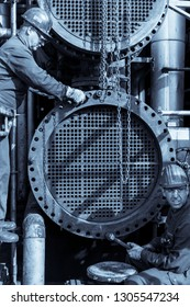 Cologne, Germany - August 3 2018: Two workers are assembling a heat exchanger. The tube sheet is visible as the channel has been removed.