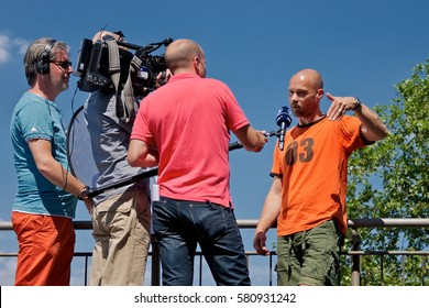 Cologne, Germany - August 5, 2013: TV-reporters of WDR broadcasting company are taking an interview with a local resident.