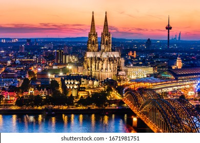 Cologne, Germany: Beautiful panoramic aerial night landscape of the gothic catholic Cologne cathedral, Hohenzollern Bridge and the River Rhine at sunset golden hour and blue hour.