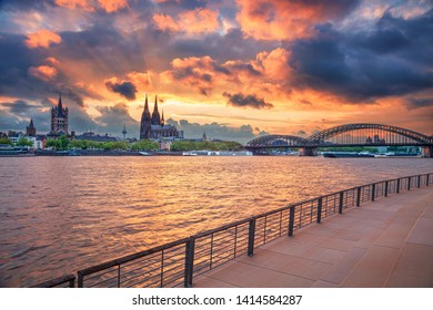 Cologne, Germany. Cityscape image of Cologne, Germany with Cologne Cathedral and Hohenzollern Bridge during dramatic sunset.