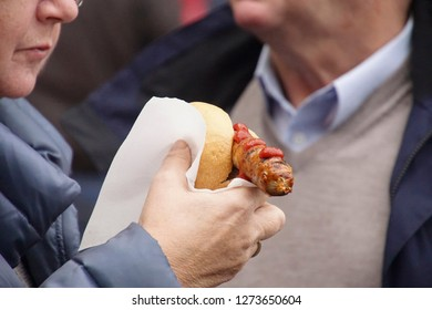 COLOGNE, GERMANY - DEC 17, 2018 - Eating a hot dog at the Christmas market,Cologne, Germany
