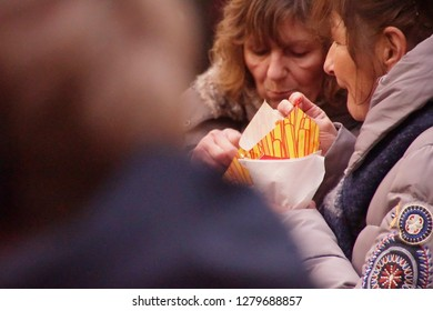 COLOGNE, GERMANY - DEC 17, 2018 - Group of women sharing French fries from the Christmas market,Cologne, Germany