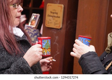COLOGNE, GERMANY - DEC 17, 2018 - Hoisting a warm drink on a cold afternoon at the Christmas market,Cologne, Germany