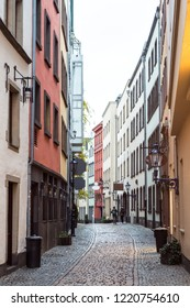 Cologne, Germany - December, 2017: Shops and tourists on the cobblestone streets of Old Town Cologne.
