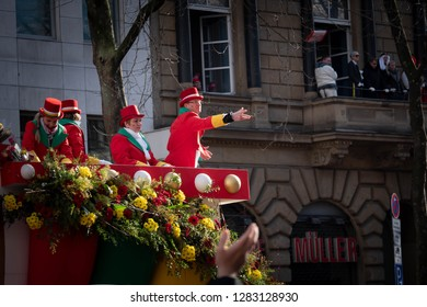 COLOGNE, GERMANY, FEBRUARY 12, 2018, Cologne street carnival, man in red top hat throwing chocolate bar to the crowd, people celebrating on balcony in the background, typical carnival scene