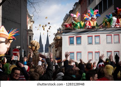 COLOGNE, GERMANY, FEBRUARY 12, 2018, Cologne street carnival, people throwing sweets from a large float, cathedral in the background, very typical carnival moment