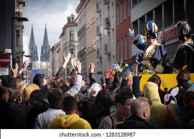 COLOGNE, GERMANY, FEBRUARY 12, 2018, Cologne street carnival, old man on a float, in traditional carnival society costume, raising his arm to the crowd, cologne cathedral in the background