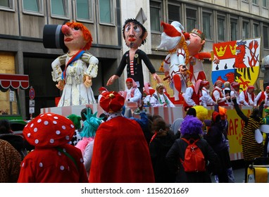 COLOGNE, GERMANY - FEBRUARY 8, 2016: Colorful floats with huge caricature figures on famous Rosenmontag (Rose Monday) parade, highlight of German and Cologne Karneval. Crowd dress up in fancy costumes
