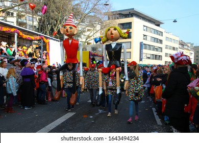 COLOGNE, GERMANY - FEBRUARY 8, 2016: Float with huge figures, marching bands and participants in funny costumes on Rosenmontag (Rose Monday) parade, highlight of German Karneval. People dress up.