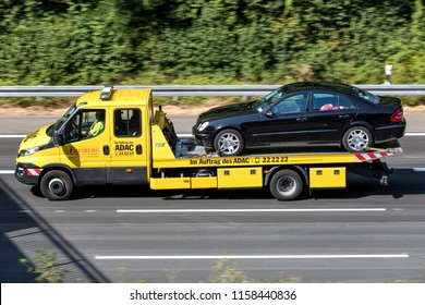 COLOGNE, GERMANY - JULY 13, 2018: ADAC flatbed recovery vehicle on motorway. German ADAC it is the largest automobile club in Europe.