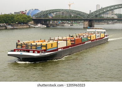Cologne, Germany - July 5 2015: Container ship BOLERO (ENI 02325839, built in China in 2003) on the River Rhine with Bridge Hohenzollernbrücke in the background.