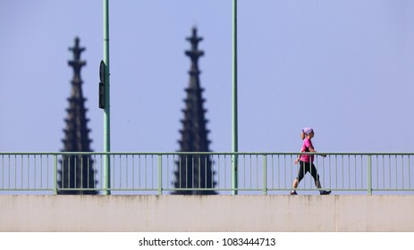 COLOGNE / GERMANY - JULY 7th 2015: Pedestrian walking on Zoo Bridge. Spires of Cologne Cathedral in the background.