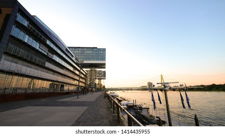 Cologne Köln, Germany june 1, 2019 Sanding at rhein shore with sunset looking at Kranhaus and city center of cologne