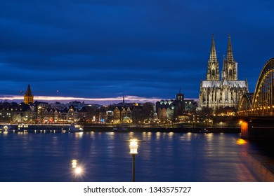 Cologne, Germany - March 12, 2019: Cologne Cathedral, Hohenzollern Bridge Panorama, view of the old town of Cologne during the golden hour. Royal blue sky. Cologne Central Station.