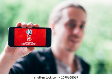 COLOGNE, GERMANY - May 06, 2018: Closeup of young man holding white iPhone with FIFA WORLDCUP 2018 LOGO on screen