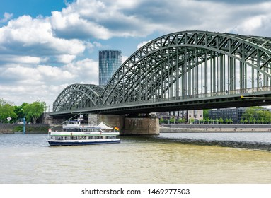 COLOGNE, GERMANY - MAY 12: Passenger ship crossing Hohenzollern bridge in Cologne, Germany on May 12, 2019. View to Triangle tower.