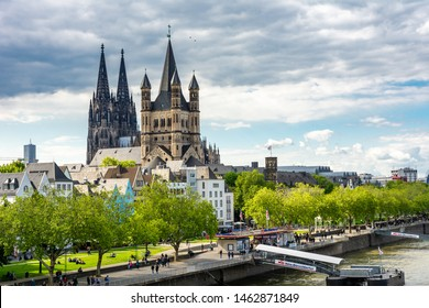 COLOGNE, GERMANY - MAY 12: Tourists at the river Rhine in Cologne, Germany on May 12, 2019. View to Cologne Cathedral and Great Sain Martin church.