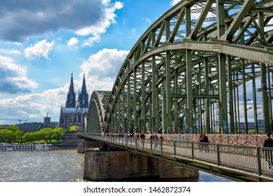 COLOGNE, GERMANY - MAY 12: Tourists on  Hohenzollern bridge in Cologne, Germany on May 12, 2019. View to Cologne Cathedral.