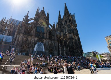 Cologne, Germany - May 2018. Local people and tourists sitting on the steps of the Cathedral and walking in the square in front of the Central Station