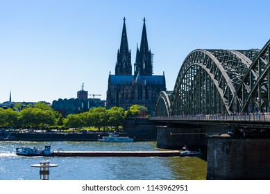 COLOGNE, GERMANY - MAY, 2018: People walking on Hohenzollern Bridge in Cologne or famous Love Locks Bridge with thousands pad locks left by lovers. In the background the majestic Gothic Cathedral.