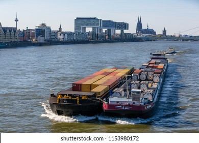 Cologne, Germany: May 5 2016: Cargo ship ST. ANTONIUS II (ENI 02332893, built in 2010) as pusher train with a barge towed alongside on the River Rhine in front of the skyline of Cologne.