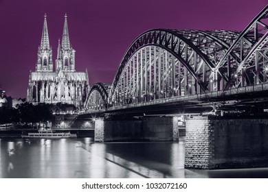Cologne, Germany. Night View Of Cologne Cathedral And Hohenzollern Bridge. Catholic Gothic Cathedral In Night Lighting.  UNESCO World Heritage Site. Black, White And Ultra Violet Colors