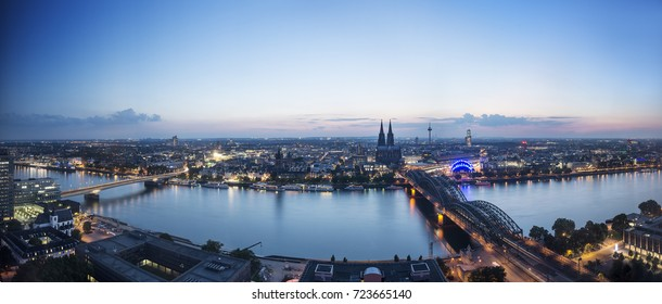 Cologne, Germany Night/Twilight time Cityscape Panorama across Rhine River to Cologne Cathedral (DOM), Hohenzollern Bridge and Köln Hauptbahnhof (Cologne Central Station)