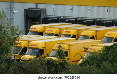Cologne, Germany - October 8, 2017: DHL courier trucks parked at a DHL warehouse shipment facility in Cologne, Germany.