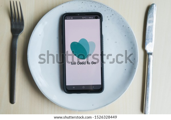 Cologne, Germany - October 9 2019: table top shot of a smartphone lying on a white plate. The logo of the to good to go application is displayed on the smartphone
