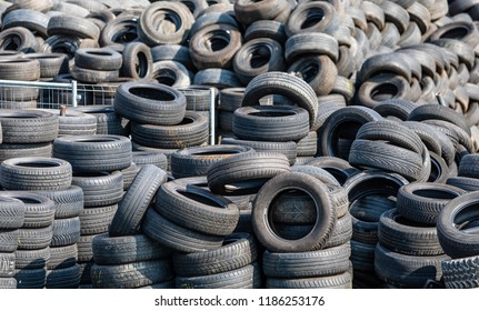 Cologne, Germany - September 2 2018: Used tires, stacked in a junkyard. The rubber will be recycled in noise protection walls or used in the incinerators of the cement industry.