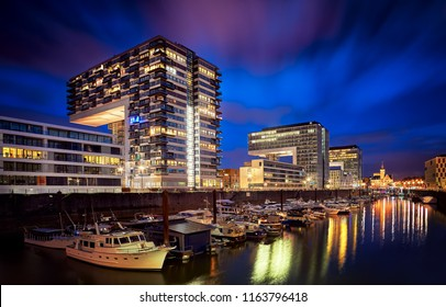 Cologne, Germany - September 5, 2015: Rheinauhafen water promenade in Cologne Koeln marina at night with boats on the water