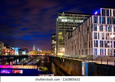 Cologne, Germany - September 5, 2015: Rheinauhafen in Cologne Koeln marina at night and the Koelner Cologne Dom Cathedral Dom on the background