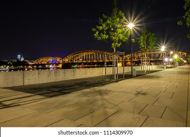 Cologne at night, Rhine Boulevard with the Hohenzollern bridge and trees in the background.