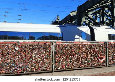 Köln (Cologne), Nordrhein-Westfalen/Deutschland -09-27-2018: Padlocks for everlasting love on the Hohenzollernbrücke over the river Rhein in Cologne (Köln) and an ICE express train passing by.