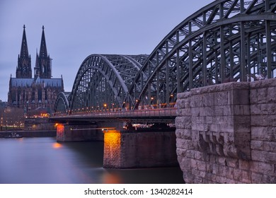 Cologne Panorama of Cologne Cathedral and the Hohenzollern Bridge in cloudy sky just before sunset.