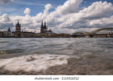 Cologne Panorama, daytime with cloudy sky on the Rhine, in the background the Cologne Cathedral the Great St. Martin's Church and the Hohenzollern Bridge. The Rhine is blowing waves.