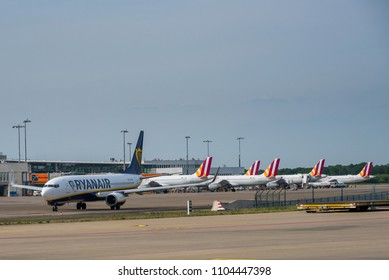 COLOGNE-BONN / GERMANY - MAY 2018 Line up of low cost carrier ariplanes at Cologne Bonn Airport. 5 Eurowings Airbusses still wearing Germanwings tail colours and one Ryanair B737 taxing for departure.
