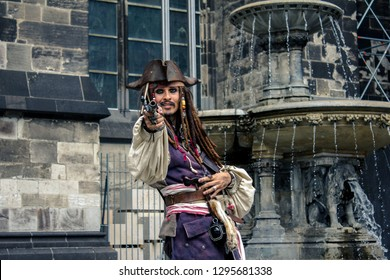 Cologne/Germany - 7/24/2017: Street artist and performer wearing the costume and image of Jack Sparrow from Pirates of the Caribbean movie directing the barrel of the gun on the camera and smiling.