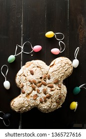 Colomba pasquale , dove, with multi colored eggs and on a wooden dark background, top view, natural window light.