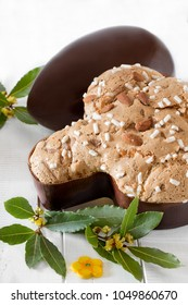 Colomba pasquale, typical italian sweet for Easter and chocolate egg on white wooden background.